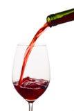 Rött vin som hälls in i ett vinexponeringsglas Arkivbild