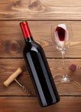 Rött vinflaska, exponeringsglas och korkskruv på trätabellen Arkivfoto