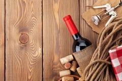 Rött vinflaska, korkar och korkskruv över trätabellbackgroun Arkivfoton