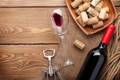 Rött vinflaska, vinexponeringsglas, bunke med korkar och korkskruv Royaltyfri Foto