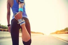 Rüttler der jungen Frau bereit, gesetztes und das Betrachten intelligente Uhr des Sports laufen zu lassen Lizenzfreie Stockfotografie
