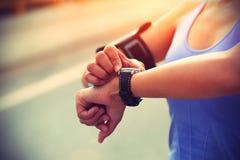 Rüttler der jungen Frau bereit, gesetztes und das Betrachten intelligente Uhr des Sports laufen zu lassen Stockfotografie