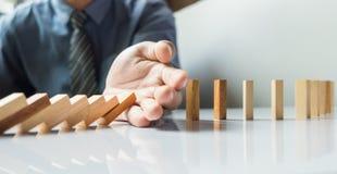 ruído contínuo ou risco dos dominós da parada da mão do homem de negócios com c Imagem de Stock
