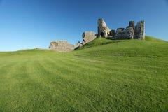 Ruína da fortaleza medieval que senta-se no monte gramíneo Fotografia de Stock Royalty Free