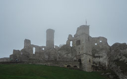 Ruína medieval do castelo que senta-se sobre o monte na névoa pesada Fotografia de Stock Royalty Free