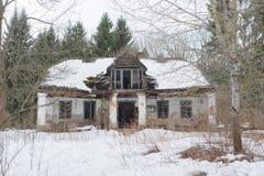 Ruína velha abandonada da casa na construção da neve da floresta do inverno Foto de Stock