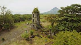 Ruínas da igreja de Cagsawa da vista aérea com o vulcão no fundo, Legazpi de Mayon da montagem, Filipinas overcast filme