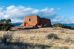 Ruínas de uma igreja espanhola da missão do adôbe velho em um prado gramíneo no parque histórico nacional dos Pecos foto de stock