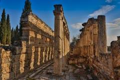 Ruínas do templo de Appollo com a fortaleza na parte traseira em Corinth antigo, Peloponnese, Grécia imagem de stock