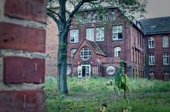 Ruïne van een groot baksteenhuis na een brand in de zolder om de Brandstichtingsdiefstal en vandalisme van de brandschade te verd stock foto's