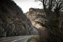 Ruïnes van middeleeuws kasteel bovenop heuvel dichtbij de rivier en de weg royalty-vrije stock foto's