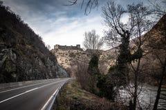 Ruïnes van middeleeuws kasteel bovenop heuvel dichtbij de rivier en de weg royalty-vrije stock foto