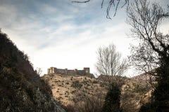 Ruïnes van middeleeuws kasteel bovenop heuvel dichtbij de rivier en de weg royalty-vrije stock fotografie