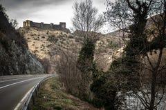 Ruïnes van middeleeuws kasteel bovenop heuvel dichtbij de rivier en de weg royalty-vrije stock afbeelding