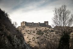Ruïnes van middeleeuws kasteel bovenop heuvel dichtbij de rivier en de weg royalty-vrije stock afbeeldingen