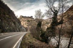 Ruïnes van middeleeuws kasteel bovenop heuvel dichtbij de rivier en de weg stock foto's