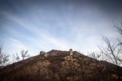 Ruïnes van middeleeuws kasteel bovenop heuvel dichtbij de rivier en de weg stock foto
