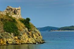 Ruïnes van oude roman vesting met zandig strand op achtergrond, Sithonia, Griekenland Stock Afbeelding