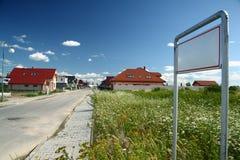Rua com as casas recentemente construídas e sinal vazio Fotos de Stock Royalty Free