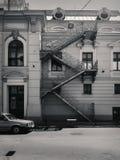 Rua com construção velha e um carro, em preto e branco imagem de stock