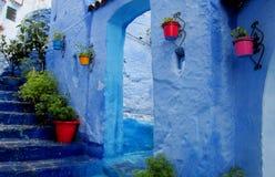 Rua com os potenciômetros de flor azuis coloridos, Marrocos de Chefchaouen Foto de Stock Royalty Free