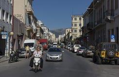 Rua com uma estrada larga, com casas de cada lado, carros, bicicletas Imagens de Stock Royalty Free