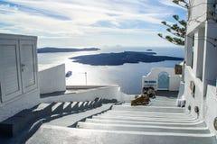 Rua da cidade branca bonita de Fira com uma vista do vulcão e do Mar Egeu fotos de stock