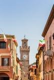 Rua da cidade com casas, torre e a bandeira italiana Foto de Stock