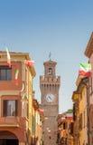 Rua da cidade com casas, torre e a bandeira italiana Foto de Stock Royalty Free