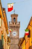 Rua da cidade com casas, torre e a bandeira italiana Fotos de Stock Royalty Free