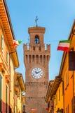 Rua da cidade com casas, torre e a bandeira italiana Fotografia de Stock Royalty Free