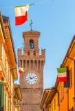 Rua da cidade com casas, torre e a bandeira italiana Fotografia de Stock