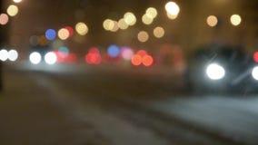 A rua da noite com bokeh ilumina-se na tempestade de neve vídeos de arquivo