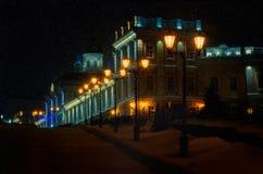 Rua da noite do inverno em uma cidade europeia A luz da lanterna ao longo da estrada com luz amarela, e na distância é Imagens de Stock Royalty Free