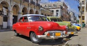 Rua de Havana com os carros velhos coloridos em um cru Imagens de Stock Royalty Free