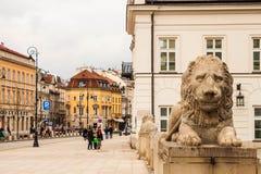 Rua de Krakowskie Przedmiescie e uma escultura de guardar o leão imagem de stock royalty free
