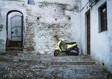 Rua de pedrinha com 'trotinette' estacionado, Granada Imagens de Stock Royalty Free