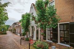 Rua encantador e quieta com as casas rústicas do tijolo e hortaliças no dia nebuloso em Drimmelen imagens de stock royalty free