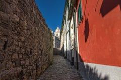 A rua estreita ao lado de uma parede de pedra antiga e de uma casa vermelha conduz à igreja na montanha, Porto Venere, Itália foto de stock royalty free