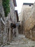 Rua estreita com as escadarias da pedra na inclinação do subúrbio medieval de Sermoneta no Lazio em Itália Foto de Stock
