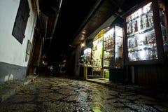 Rua estreita com loja de lembrança tarde na noite no quadrado de Bascarsija de Sarajevo Imagens de Stock