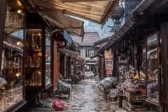 Rua estreita do distrito de Bascarsija de Sarajevo, com os ofícios típicos do cobre do metal que estão sendo produzidos com técni Foto de Stock Royalty Free