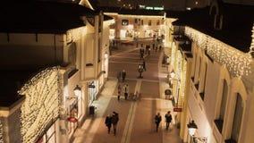 Rua leve acolhedor com construções de loja amarelas iluminadas e os povos de passeio vídeos de arquivo