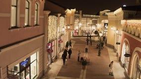 Rua leve acolhedor com construções de loja amarelas iluminadas e os povos de passeio video estoque