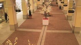 Rua leve agradável com construções de loja amarelas iluminadas e os povos de passeio video estoque