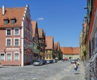 Rua medieval com a mulher que anda com as flores cortadas frescas imagens de stock