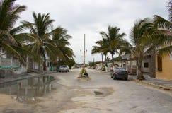 A rua mexicana da aldeia piscatória durante a estação das chuvas com carros estacionou ao longo dos lados e do saco do lixo no me foto de stock royalty free