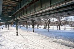 Rua nevado debaixo das trilhas do trem Imagem de Stock