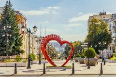 Rua pedestre no centro residencial velho da cidade Banco do amor na forma de um coração com potenciômetros de flor Imagem de Stock