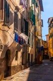 Rua pedestre pequena da cidade de Itália em parte nas sombras com secagem da roupa e de máscaras locais imagens de stock royalty free